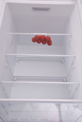 Cherry tomatoes in open empty refrigerator.