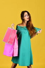 Shopping and leisure concept. Lady stands on yellow background
