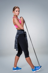 Full length image of a pretty fitness woman doing exercise with