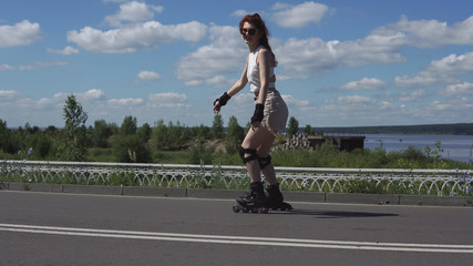 young girl in shorts and tops skates on roller skates