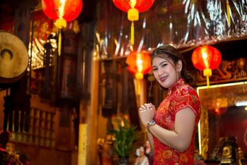 Portrait of beautiful asian woman wear cheongsam on light of lantern background,Happy chinese new year,Thailand people