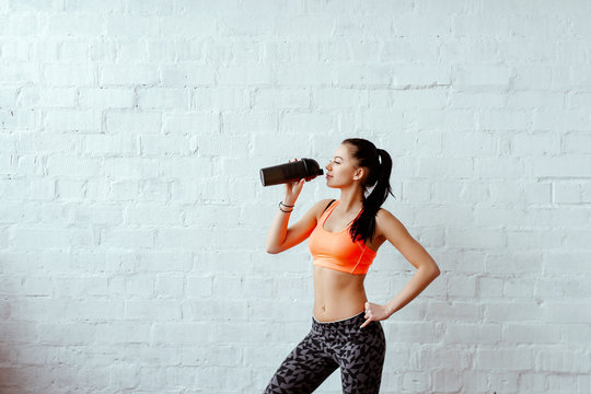the sports girl the brunette in an orange topic with a fitness shaker