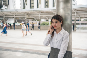 Portraits of beautiful asian woman look confidence is standing and holding cellphone . she using smartphone calling to conversation with customer.