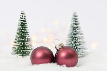 Christbaumkugeln mit Tannen im Schnee