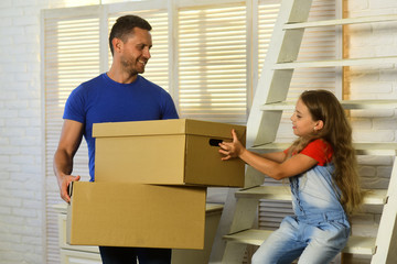 Daughter and father hold boxes and unpack or pack