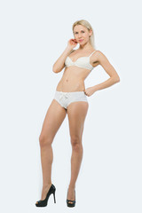 Full length of a beautiful Blonde Woman poses in white underwear