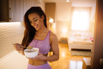 Young fit sporty girl eating her healthy breakfast.
