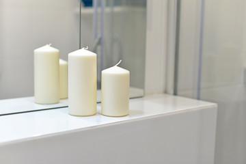 Białe świece odbijające się w lustrze