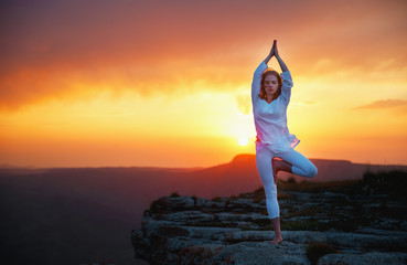 Fototapete - woman practices yoga and meditates   on sunset mountains