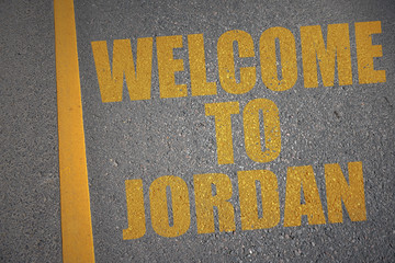 asphalt road with text welcome to jordan near yellow line.