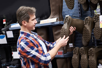 Man chooses rubber boots for hunting and fishing in store
