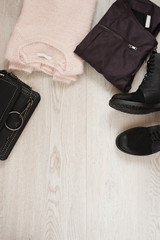 Women trendy fashion clothes collage with sweater, leather pants, military boots and bag. Flat lay