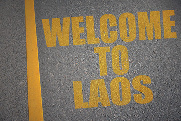 asphalt road with text welcome to laos near yellow line.