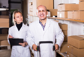 Portrait of different ages couple with carton boxes in warehouse