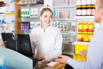 Professional pharmaceutist helping customer