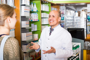 Pharmacist and client in pharmacy .