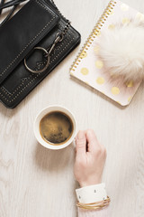 Top view woman hand holding cup of black coffee on flat lay. Workspace with notebook in pink and gold, fashion handbag and fur ball