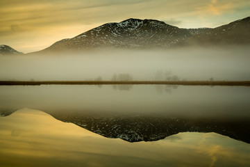 landscape view of scotland and loch tulla at blue hour in winter with calm waters and fog