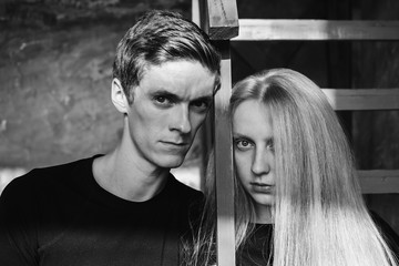 A young man and young blonde woman with long hair. Problems and difficulties in relations. The difficult situation in life. Conceptual photography. Actor play. Hard shadows. Woman and man portrait