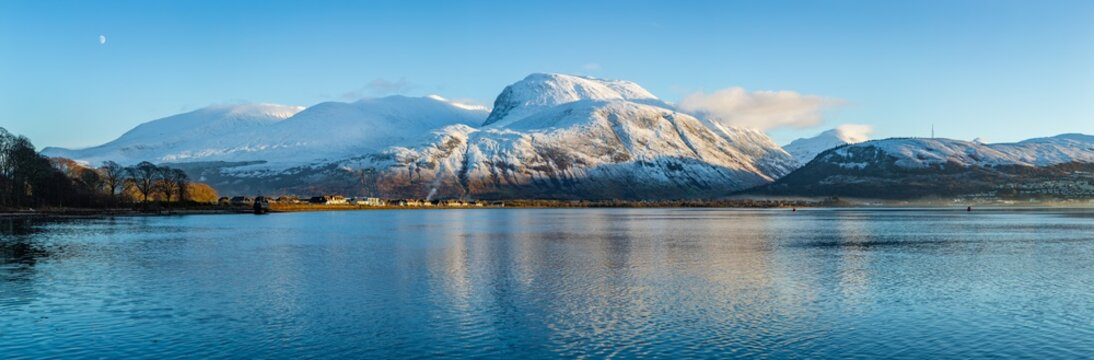 landscape view of scotland and ben nevis near fort william in winter with snow capped mountains and calm blue sky and water