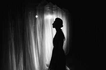 Woman silhouette. The white long canopies are illuminated by the light of the lantern on a dark night. Conceptual photography.