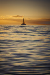 Sailboat floating at sea during golden sunset