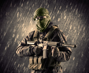 Armed terrorist man with mask on rainy background