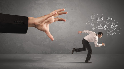 Business person running away from big hand