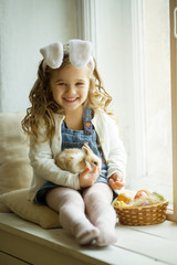 Cute little child girl is wearing bunny ears on Easter day holding little rabbit