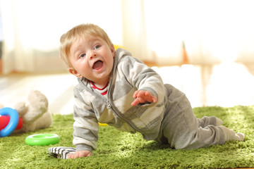 Baby crawling on a green carpet at home