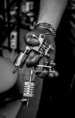 Hand of skin master with a tattoo machine.
