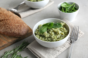 Dish with delicious spinach risotto on table