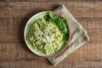 Plate with delicious spinach risotto on wooden table