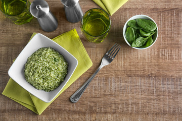 Dish with tasty spinach risotto on table, top view
