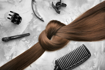 Professional hairdresser's set and strand of brown hair on grey background