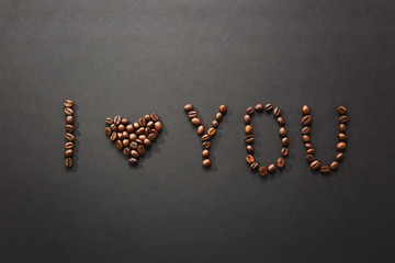 Top view of I love you letter - I heart U words made from coffee beans on black background for design. Saint Valentine's Day card on fabruary 14, holiday concept. Copy space for advertisement.