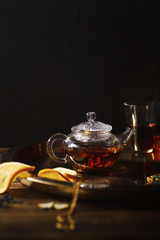 Small glass teapot and glasses with hot black tea, dried rose petals, pocket magnifier on golden chain, squeezed orange slice on golden tray. Evening light. Side view.