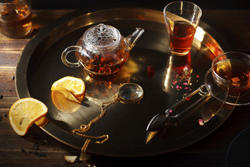 Small glass teapot with hot black tea, cup, glasses, dried rose petals, pocket magnifier on golden chain, squeezed orange slice on golden tray on wooden background. Evening light. Overhead view.