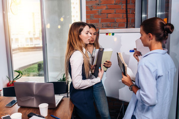 Three young businesswomen sharing new business ideas holding notes standing at whiteboard in office