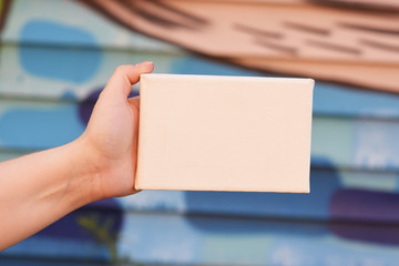 Female hand with tiny canvas in front of urban background