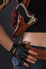 Close up of sexy girl with gun in belt