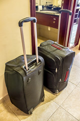 Two black suitcases with long handles in the hotel room stand on the floor.