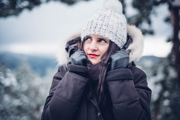 Beautiful woman poses in snowy landscape.