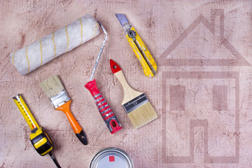 Assorted work tools on plaster background