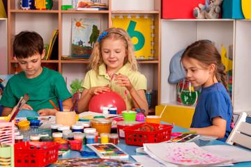 Small students with teacher finger painting in art school class. Teacher cheers children in kindergarten. Newcomer in children's team. Craft drawing education develops creative abilities of children.