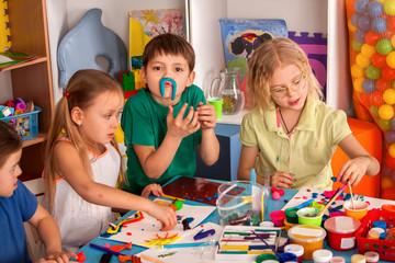 Child dough play in school. Plasticine for children. mold from plasticine in kindergarten. Kids knead modeling clay with hands in preschool. Newcomer in children's team.