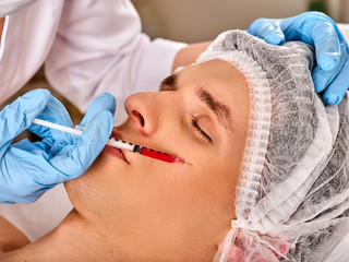 Filler injection for male face. Plastic aesthetic facial surgery in beauty clinic. Man giving anti-aging injections for pull up face contour. Doctor hand in medical gloves with syringe injects drug.
