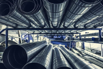 Stack of steel or metal pipes or round tubes as industrial background with perspective