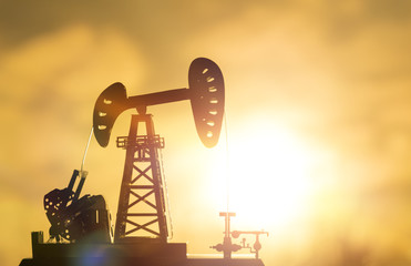 silhouette of an oil drilling pump against a background of sun rays in the sunset