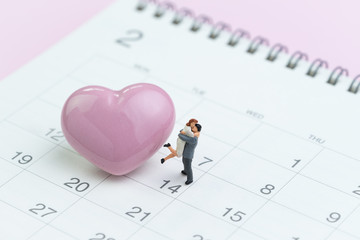 Miniature couple standing with shiny pink heart shape on 14th Feb calendar on pink background as Valentine's day